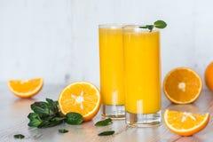 Zumo de naranja con la menta en vidrios en el fondo de madera ligero Imagenes de archivo
