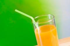 Zumo de naranja con la paja en el concepto de madera de la nutrición de la tabla Fotos de archivo