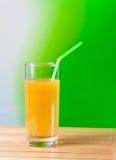 Zumo de naranja con la paja en el concepto de madera de la nutrición de la tabla Imagen de archivo
