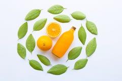 Zumo de naranja con las hojas verdes en el fondo blanco fotos de archivo