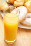 Zumo de naranja con las tortas sobre la visión Fotografía de archivo