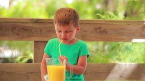 Zumo de naranja de la bebida del niño pequeño almacen de video