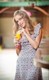 Zumo de naranja del vidrio de consumición de la mujer Foto de archivo