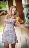 Zumo de naranja del vidrio de consumición de la mujer Foto de archivo libre de regalías