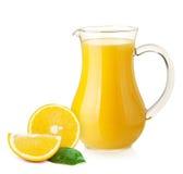 Zumo de naranja en jarra y naranjas Imagenes de archivo