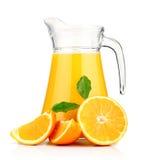 Zumo de naranja en jarra y naranjas. Imágenes de archivo libres de regalías