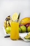 Zumo de naranja en las frutas de cristal y mezcladas   foto de archivo libre de regalías