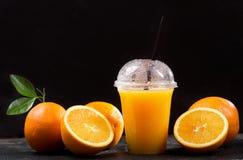 Zumo de naranja en taza plástica para llevar con las frutas frescas Foto de archivo