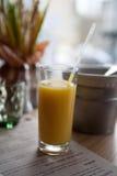 Zumo de naranja en un vidrio con una paja en un café Fotografía de archivo