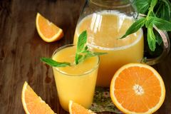 zumo de naranja en un vidrio y un jarro foto de archivo