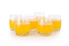 Zumo de naranja en vidrios en el fondo blanco. Foto de archivo
