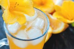 Zumo de naranja frío con el hielo, adornado con un primer amarillo de la flor del lirio fotos de archivo libres de regalías