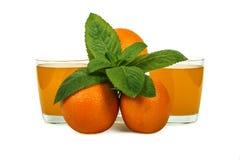 Zumo de naranja fresco con la menta en una taza de cristal aislada en el fondo blanco Naranjas y jugo frescos en un fondo blanco, Imagenes de archivo