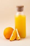 Zumo de naranja fresco en una botella de cristal y una naranja en un beige de la luz Imagenes de archivo
