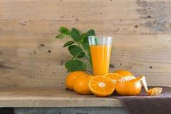 Zumo de naranja fresco en vidrio en la madera a creativo para el diseño imágenes de archivo libres de regalías