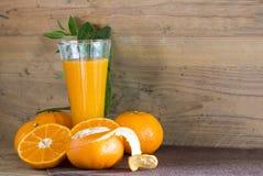 Zumo de naranja fresco en vidrio en la madera a creativo para el diseño foto de archivo libre de regalías
