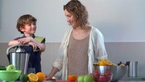 Zumo de naranja fresco hecho en casa caucásico joven de la madre y del niño en cocina con el Juicer eléctrico almacen de video