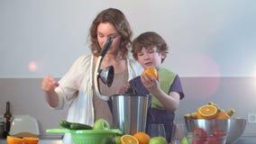 Zumo de naranja fresco hecho en casa caucásico joven de la madre y del niño en cocina con el Juicer eléctrico metrajes