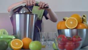 Zumo de naranja fresco hecho en casa del muchacho caucásico divertido joven en cocina con el Juicer eléctrico y la sonrisa metrajes