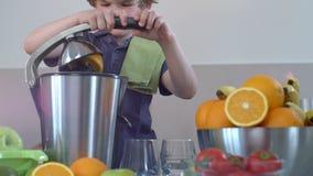 Zumo de naranja fresco hecho en casa del muchacho caucásico divertido joven en cocina con el Juicer eléctrico y la sonrisa almacen de video