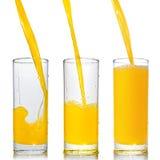 Zumo de naranja poring en el vidrio Fotos de archivo