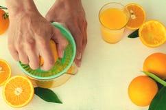 Zumo de naranja recientemente exprimido por las manos del ` s de los hombres, en juicer de la turquesa en el fondo blanco Imagen de archivo libre de regalías