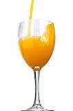 Zumo de naranja vertido en un vidrio de vino Imágenes de archivo libres de regalías