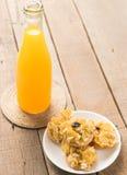 Zumo de naranja y bocado o galleta en cierre para arriba en la madera de la tabla Foto de archivo libre de regalías
