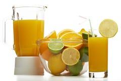 Zumo de naranja y mezclador con la fruta Fotografía de archivo