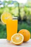 Zumo de naranja y rebanadas de naranja aislados en la tabla de madera, en g Imagen de archivo