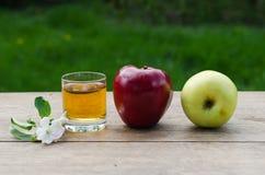Zumo y manzanas de manzana rojos y verdes en una tabla de madera Foto de archivo