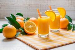 2 zumos de naranja con las rebanadas anaranjadas, paja Fotos de archivo
