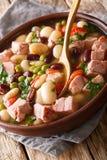 Zuppa di fagioli deliziosa con il prosciutto, i pomodori ed il primo piano delle erbe in una ciotola verticale immagine stock