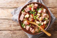 Zuppa di fagioli deliziosa con il prosciutto, i pomodori ed il primo piano delle erbe in una ciotola vista superiore orizzontale fotografia stock
