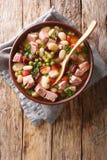 Zuppa di fagioli deliziosa con il prosciutto, i pomodori ed il primo piano delle erbe in una ciotola Vista superiore verticale immagine stock libera da diritti