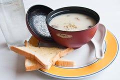 Zuppa di fungo con pane sulla tazza rossa. Fotografia Stock