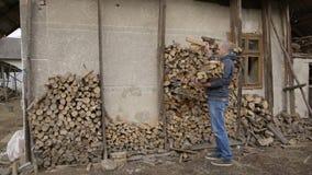 Zurück im Dorf in Ukraine kommt Mann in das Holz, im Ofen anzuzünden stock footage
