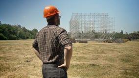 Zurück vom überzeugten Erbauer, der Metallbau auf Hintergrund, stehend im Sturzhelm auf Strohfeld betrachtet stock footage