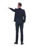 Zurück vom Geschäftsmann, der mit der Hand in der Tasche zeigt Lizenzfreie Stockfotografie