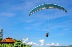 Zurück vom Gleitschirmfliegenmann im blauen Himmel an Camboinhas-Strand, Niteroi, Rio de Janeiro, Brasilien Lizenzfreie Stockbilder
