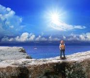 Zurück vom jungen Mann, der auf Felsenklippe steht und zum Meer schaut Stockfotos