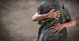 Zurück vom Soldaten, der gegen braunen Hintergrund mit Schmutzüberlagerung umarmt stockfotografie