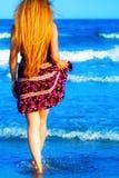 Zurück von der blonden reizvollen Frau, die in das Meer geht Stockfotografie