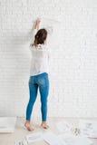 Zurück von der Frau, die ihre Skizze auf Wand hängt Lizenzfreie Stockfotos