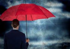 Zurück von der Geschäftsfrau mit Regenschirm herein gegen Sturm mit Schmutzüberlagerung Stockfotografie