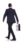 Zurück von einem gehenden Geschäftsmann, der einen Aktenkoffer anhält Lizenzfreies Stockbild