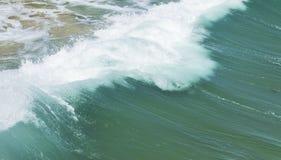 Zurück von einer brechenden Welle, wie sie das Ufer schlägt Lizenzfreies Stockfoto