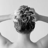 Zurück von einer Frau in einer Dusche, die ihr Haar, ihren Kopf von Seifenlösungen in Schwarzweiss voll massierend shampooing ist Stockbild