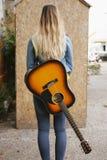Zurück von einer Frau mit acustic Gitarre Lizenzfreie Stockfotos