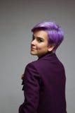 Zurück von einer Frau mit dem Violett-kurzhaar, das einen violetten Mantel trägt Lizenzfreie Stockfotografie